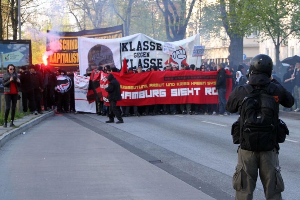 Die Demonstration bleibt stehen, legt die Vermummung ab und hört auf zu werfen.